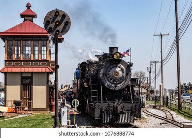 Strasburg, PA, USA - April 14, 2018:  A smokey steam locomotive operated by the Strasburg Rail Road stops at the train station in Lancaster County, PA.