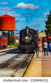 Strasburg, PA, USA - October 6, 2015: Tourists photograph the Strasburg Rail Road steam locomotive arriving at the train station.
