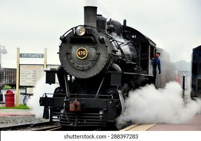 Strasburg, Pennsylvania - June 5, 2015:  A vintage locomotive with its engineer and puffs of white steam pulling into the Strasburg Railroad station  *