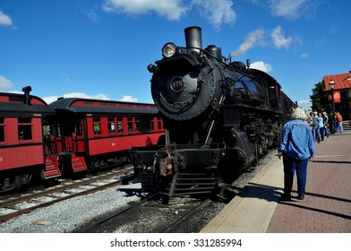 Strasburg, Pennsylvania - October 16, 2015:  Awaiting passengers watch a vintage steam locomotive arriving at the Strasburg Railroad station