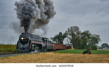 STRASBURG, UNITED STATES - Oct 06, 2019: Steam Freight Train Passing an Antique Tractor with a Woman Seating in the Farm land with Black Smoke and Steam on an Autumn Day