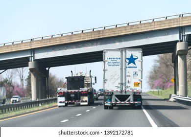 Strasburg, USA - April 18, 2018: Traffic cars on interstate highway i-81 in Virginia with Landstar transportation trailer, hauler truck with sign for leasing and sale under exit overpass bridge