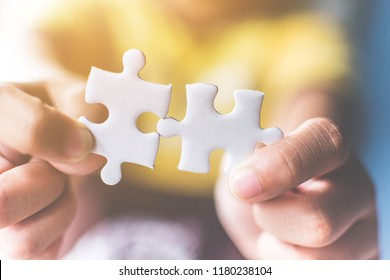 Strategic management and business solutions for success, Hand connecting jigsaw puzzle