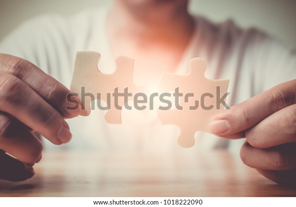 Strategic management and business solutions for success, Hand of male connecting jigsaw puzzle