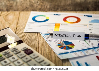Strategic Plan motivational business finance budget concept with charts and graphs and calculator on wooden board