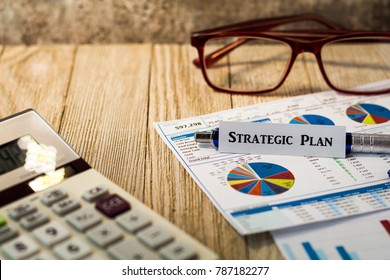 Strategic Plan motivational concept with charts and graphs and calculator on wooden board
