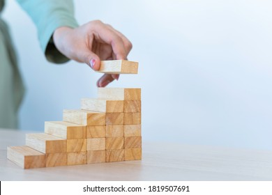 The strategic thinking of businesswomen Connecting wood blocks is like building a business with a solid foundation to develop to progress And business growth, business expansion concept