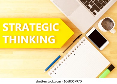 Strategic Thinking - linear text arrow concept with notebook, smartphone, pens and coffee mug on desktop - 3D render illustration.