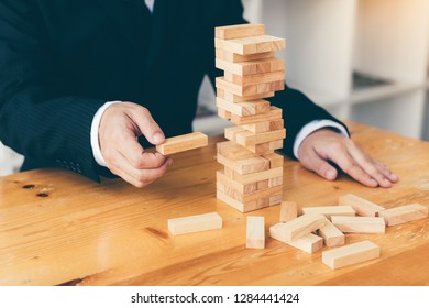 Strategic thinking and risk by business people pulls wooden blocks from the group.