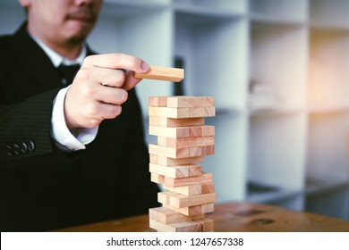 Strategy concept and hand of businessman playing wood blocks stacks game with planning.