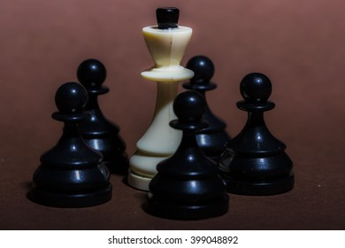 Strategy Concept Still Life Image of White King Chess Piece Surrounded by Group of Black Pawns on Rose Colored Background