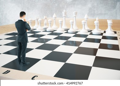 Strategy concept with thinking businessman and white chess pieces standing on huge chessboard with concrete wall in the background. Sideview, 3D Rendering
