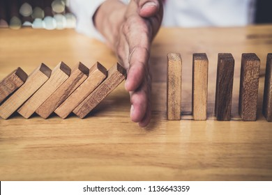 Strategy and successful intervention concept for business, businessman hand Stopping Falling wooden Dominoes effect from continuous toppled or risk.