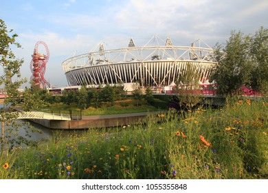 Stratford, London, England - September 1, 2012. Olympic Stadium and the ArcelorMittal Orbit shown amidst the bright and colourful plants and flowers in the Queen Elizabeth Park