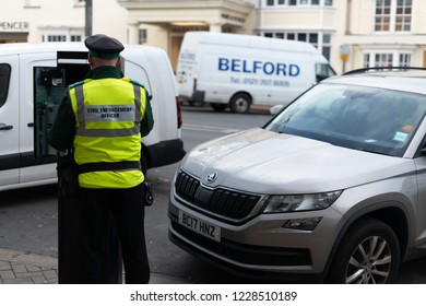 stratford upon avon warwick England UK  November 8th 2018 civil enforcement officer traffic warden collects money from parking meter in busy high street