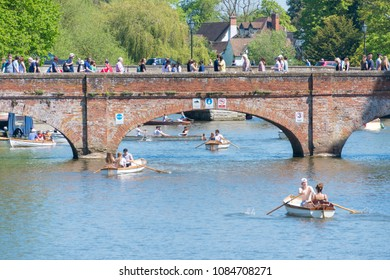 stratford upon Avon Warwickshire England UK May 6th 2018 bank holiday crowds of people enjoying the river avon in rowing boats heading under very vintage arched bridge with lots of passers by