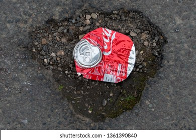 stratford upon Avon Warwickshire  England UK March 23rd 2019 crushed coca cola can and pothole illustrating the damage done to the world by large corporations like Coke