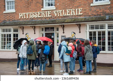 Stratford upon Avon Warwickshire England UK April 4th 2019 crowd stood outside patisserie valerie with rain falling and umbrellas indicating lots of problems