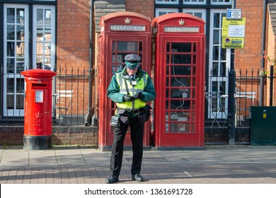 Stratford upon Avon Warwickshire England UK March 26th 2019 traffic warden or civil enforcement officer writes parking ticket with iconic British red telephone phone box and post in background