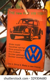 STRATFORD-UPON-AVON, UK - 4 October 2015: Vintage tin orange advertising board for Volkswagen Beetle, attached with a clothes peg to a gate, at a street flea market.