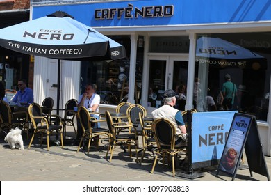 Stratford-upon-Avon, Warwickshire, England, UK. 15 May 2018.  People sitting at tables and chairs outside a Caffe Nero coffee shop.
