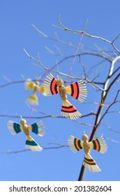 Straw artificial birds hanging by a thread