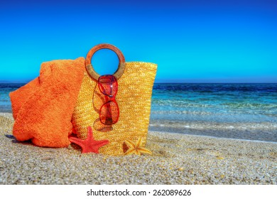 straw bag, beach towel and sunglasses on the sand in hdr