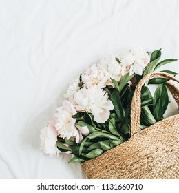 Straw bag with white peony flowers on white background. Flat lay, top view summer floral concept.