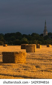 Straw bales in a field with golden evening light and stormy skys in England at Harvest time