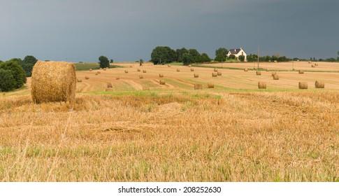 Straw bales landscape with dark stormy sky