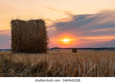 Straw bales on cloudy sky background at sunset