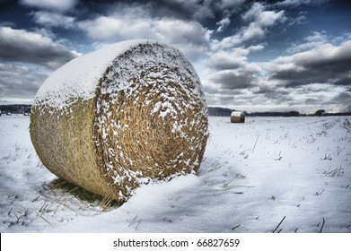 Straw bales on farmland in winter with blue cloudy sky