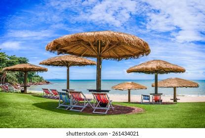 Straw Beach Umbrellas against Beach Backdrop