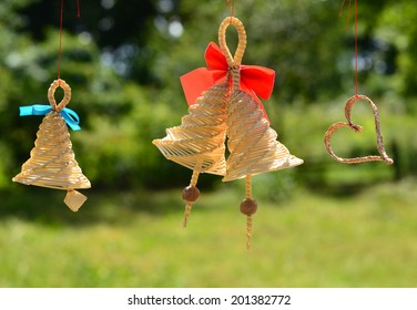 Straw bells and and heart hanging on a tree