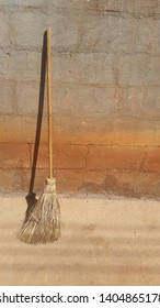 A straw broom that is leaning against the wall of a house. A broom that is used by witches to fly. Broom with wooden stick.