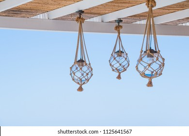 Straw cover the roof of a seaside terrace or veranda with hanging lantern and view to blue sky.many light bulbs decorated with ropes, net at the ceiling of the restaurant