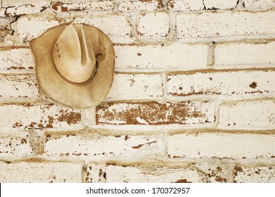 9a8c1147bf1 a straw cowboy hat hanging on an brick adobe wall that was white washed  with open