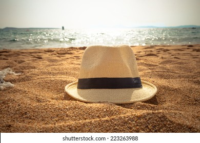 straw fedora hat on sandy beach