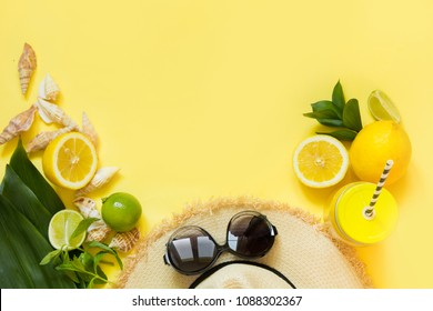 Straw foman's hat, sun glasses and beach accessory with detox citrics water on yellow. Top view. Flat lay. Space for text.
