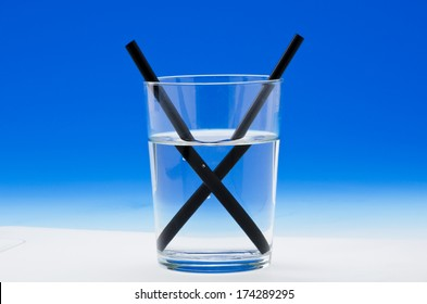 A straw in a glass of water shows light refraction. Blue background.