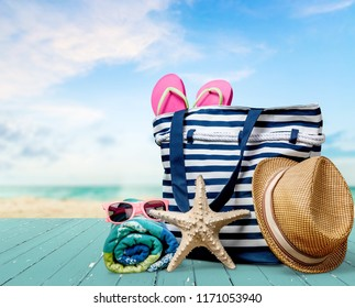 Straw hat, bag,  flip flops on a tropical beach