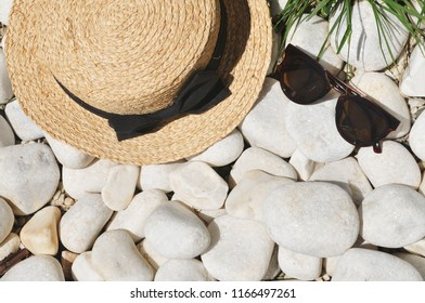 Straw hat with a black bow and sunglasses on a white pebble stones