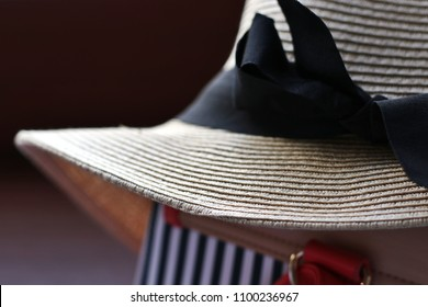Straw Hat with Blackk Bow on a Striped Bag