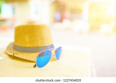 Straw hat and blue sunglasses on a hot day off on the table. Vacation concept