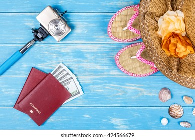 Straw hat, camera, passports with money and flip-flops laying on blue wooden background.