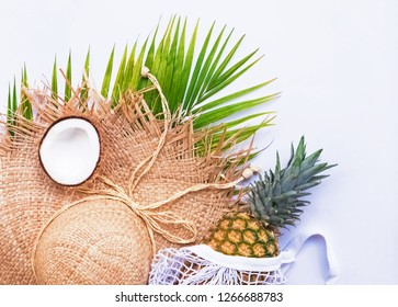 Straw hat, coconut half and pineapple on the white background. Summer tropic holidays concept.