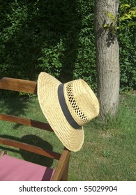 Straw hat with detail of a wooden chair