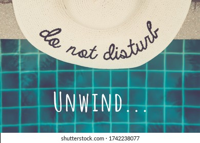 Straw hat with Do not disturb wording at the pool edge with palm reflections in the water. Relax vacation, sun protection, travel fashion concept. Toned image with Unwind... wording
