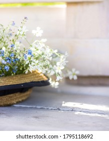 A straw hat with a flowers on the background of an white fence.