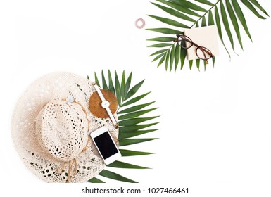 Straw hat, mobile phone, glasses and tropical palm leaf flat lay travel background. Summer travel concept